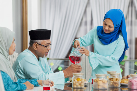 Photo pour Muslim woman serving beverage to her parent - image libre de droit