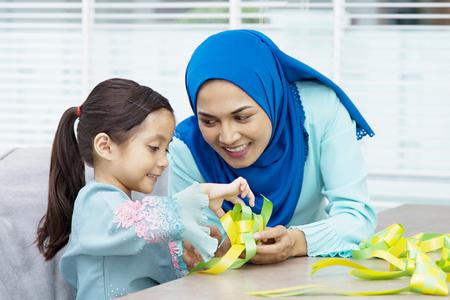Photo pour Muslim woman guiding her daughter in weaving ribbon ketupats - image libre de droit