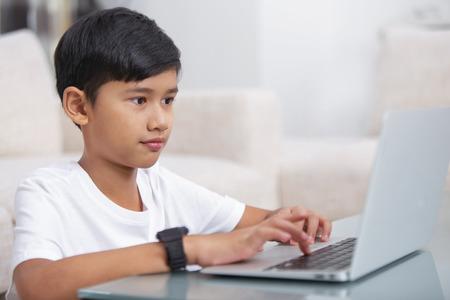 Photo pour Boy using a laptop - image libre de droit