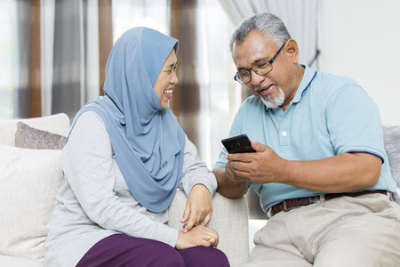 Photo pour Senior couple checking the smartphone - image libre de droit