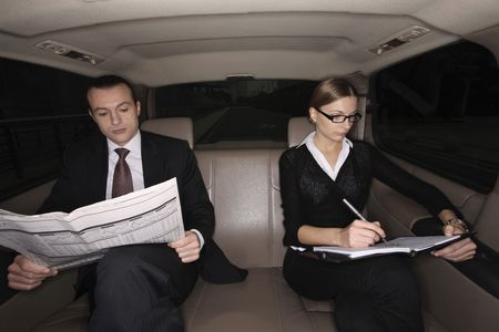 Businessman reading newspaper, businesswoman writing on an organizer in the car