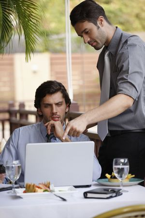 Businessmen discussing work over lunch at restaurant