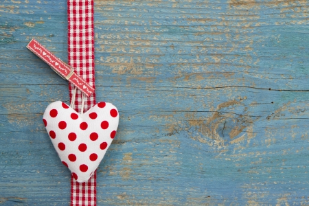 Handmade heart shape against blue wooden surface