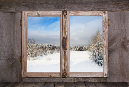 Photo pour Snowy winter landscape in january. View out of an old rustic wooden window. - image libre de droit