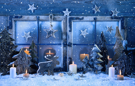 Photo for Outdoor advent window decoration in blue color with wood and burning candles. - Royalty Free Image