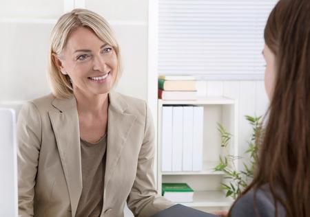 Foto de Mature businesswoman in a job interview with a young woman. - Imagen libre de derechos