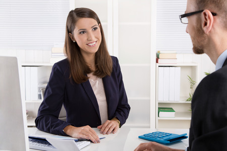 Photo pour Customer and smiling female financial agent in a discussion at desk. - image libre de droit
