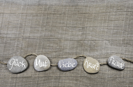 Foto de Good wishes wooden background with stones and german text for luck, courage, love, power and happiness. - Imagen libre de derechos