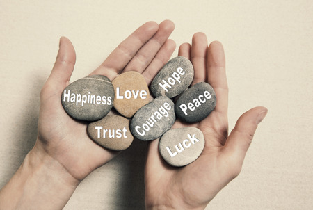 Foto de Inner balance concept: hands holding stones with text for happiness, love, trust, courage, hope, peace and luck. - Imagen libre de derechos