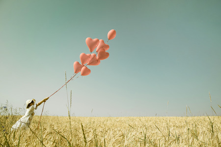 Foto de Young romantic girl in summertimes with red heart balloons walking in a field of wheat. - Imagen libre de derechos