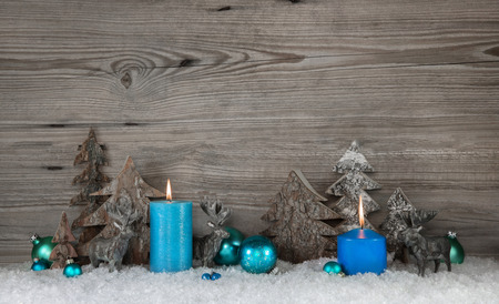 Photo pour Rustic wooden christmas background with two blue turquoise candles, deers and snow for decorations. - image libre de droit