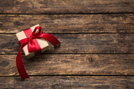 Foto de One present with an red big ribbon on old wooden dark brown background for christmas. - Imagen libre de derechos
