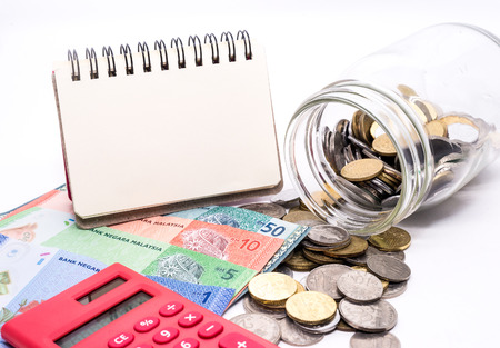 Foto de Jar of Malaysia Coins, Ringgit banknotes, red calculator and blank notepad for text. White background. Financial Concept.Shallow Depth of field - Imagen libre de derechos