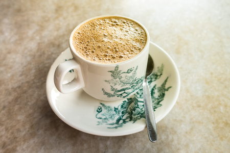 Photo for Frothy Chinese Chai/Coffee with milk in vintage cup and saucer. Breakfast drink. Shallow depth of field - Royalty Free Image