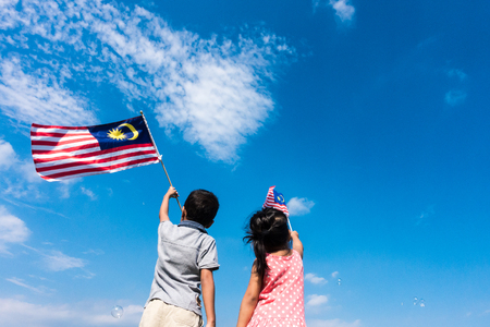 Photo pour Unknown kids/brother and sister waving the Malaysia Flag. Independence Day & Merdeka Concept. Blue sky and copy space. - image libre de droit