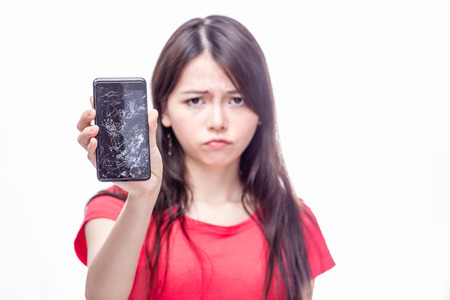 Photo for Frowning Chinese woman, OOF,  holding cell phone with cracked screen - Royalty Free Image