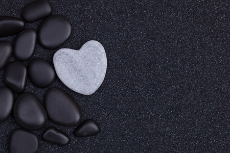 Foto de Black stones with grey zen heart shaped rock on  grain sand - Imagen libre de derechos