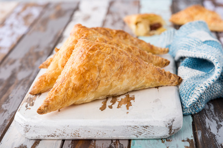 Photo for Puff pastry triangles filled with apples, dutch appelflappen on old cutting board. Homemade food concept, close up. - Royalty Free Image