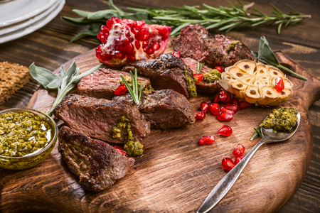 Photo pour Kangaroo meat steak with green pesto and pomegranate on wooden cutting board. Helthy holiday food concept. Selective focus. - image libre de droit