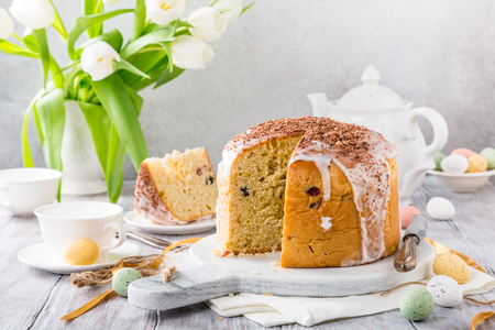 Photo for Holidays breakfast concept with copy space. Easter orthodox sweet bread, kulich and colorful quail eggs with white tulips. - Royalty Free Image