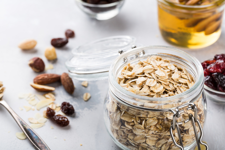 Photo for Ingredients for homemade oatmeal granola in glass jar. Oat flakes, honey, raisins and nuts. Healthy breakfast concept with copy space. - Royalty Free Image
