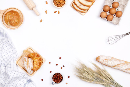 Photo for Homemade breads or bun, croissant and bakery ingredients, flour, almond nuts, hazelnuts, eggs on white background, Bakery background frame, Cooking breakfast concept. Flat lay, Top view and copy space. - Royalty Free Image
