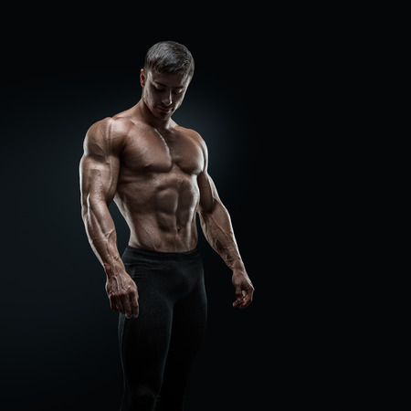 Photo for Muscular and fit young bodybuilder fitness male model posing over black background - Royalty Free Image