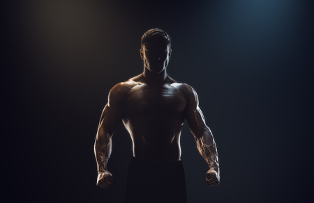 Foto per Silhouette of a strong fighter. Confident young fitness man with strong hands and clenched fists. Dramatic light. - Immagine Royalty Free