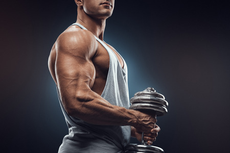 Photo pour Young man with dumbbell prepare to flexing muscles over dark background. Strong athlete in activewear ready to doing exercise with dumbbell confidently looking forward. - image libre de droit