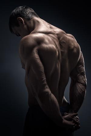 Photo pour Handsome muscular male model bodybuilder preparing for fitness training turned back. Studio shot on black background. - image libre de droit