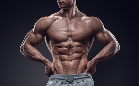 Foto de Handsome power athletic young man with great physique. Strong bodybuilder with six pack perfect abs shoulders biceps triceps and chest. Image have clipping path - Imagen libre de derechos