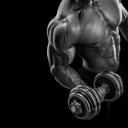 Photo pour Closeup of a handsome power athletic guy male bodybuilder doing exercises with dumbbell. Fitness muscular body on dark background. - image libre de droit