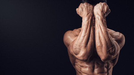 Foto de Two Power Hands in Front of Face. Closeup of a man39s fists and abs. Strong man39s arm with muscles and veins. - Imagen libre de derechos