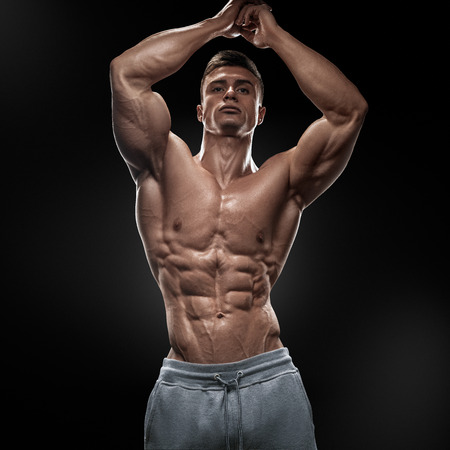 Foto de Strong athletic man fitness model torso showing six pack abs. Isolated on black background. - Imagen libre de derechos