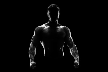 Foto de Silhouette of a strong fighter. Confident young fitness man with strong hands and clenched fists. Dramatic light. - Imagen libre de derechos
