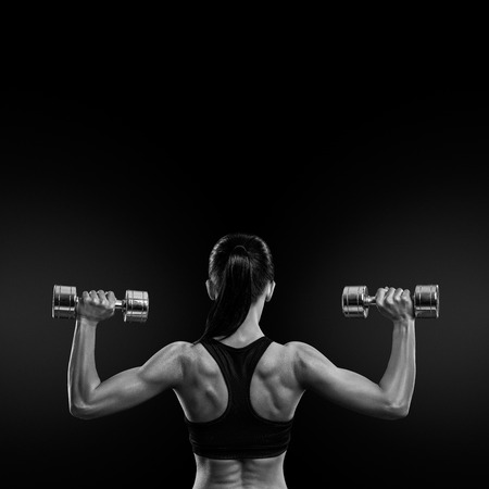 Photo pour Fitness sporty woman in training pumping up muscles of the back and hands with dumbbells. Black and white concept image - image libre de droit