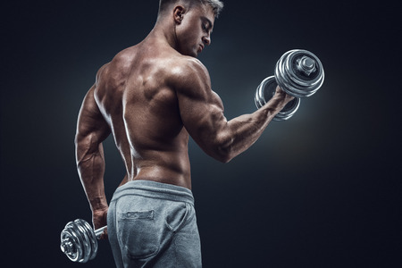 Foto de Handsome power athletic man in training pumping up muscles with dumbbells. Strong bodybuilder with six pack perfect abs shoulders biceps triceps and chest. - Imagen libre de derechos