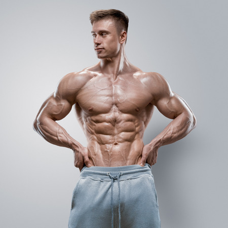 Photo for Handsome power athletic young man with great physique. Strong bodybuilder with six pack perfect abs shoulders biceps triceps and chest. Studio shot on white background - Royalty Free Image
