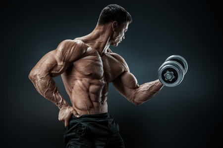 Foto de Handsome power athletic man in training pumping up muscles with dumbbell. Strong bodybuilder with six pack perfect abs shoulders biceps triceps and chest - Imagen libre de derechos