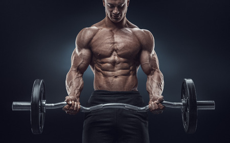 Foto de Closeup portrait of a muscular man workout with barbell at gym. Brutal bodybuilder athletic man with six pack perfect abs shoulders biceps triceps and chest. Deadlift barbells workout. - Imagen libre de derechos