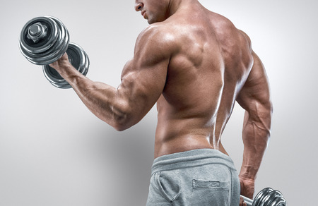 Foto per Handsome power athletic man in training pumping up muscles with dumbbell. Strong bodybuilder with six pack perfect abs shoulders biceps triceps and chest. Image with clipping path - Immagine Royalty Free