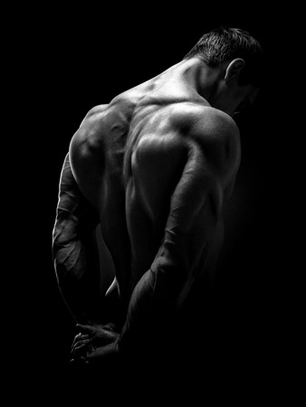 Foto de Handsome muscular male model bodybuilder preparing for fitness training turned back. Studio shot on black background. Black and white photo. - Imagen libre de derechos