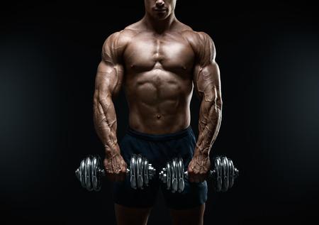 Foto de Handsome power athletic guy bodybuilder doing exercises with dumbbell. Fitness muscular body on dark background. - Imagen libre de derechos