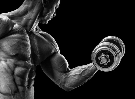 Foto de Handsome power athletic man in training pumping up muscles with dumbbell. Strong bodybuilder with six pack perfect abs shoulders biceps triceps and chest. Black and white image - Imagen libre de derechos