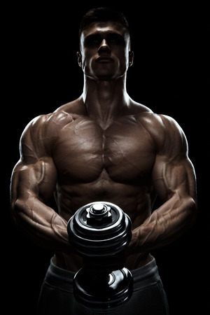 Foto de Silhouette of a bodybuilder. Power athletic man pumping up muscles with dumbbell. Confident young fitness man with strong core muscles, power hands and clenched fists. Dramatic light. - Imagen libre de derechos