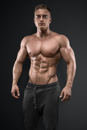 Photo for Handsome power athletic man posing on black background. Strong bodybuilder with six pack, perfect abs, shoulders, biceps, triceps and chest - Royalty Free Image