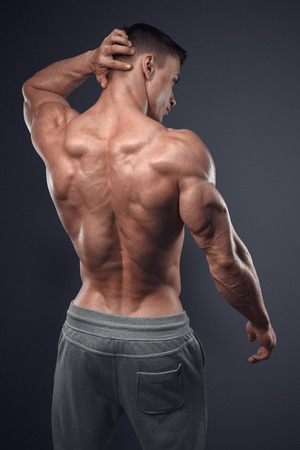 Photo pour Handsome power athletic man turned back. Isolated over black background. Strong bodybuilder with shoulders, biceps, triceps and chest - image libre de droit