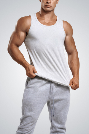 Photo pour Studio shot of a handsome young fitness man wearing white blank tank top isolated on white background - image libre de droit