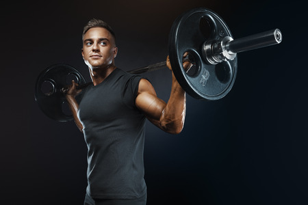 Foto de Closeup portrait of professional bodybuilder workout with barbell on black background. Muscular man training squats with barbells over head - Imagen libre de derechos