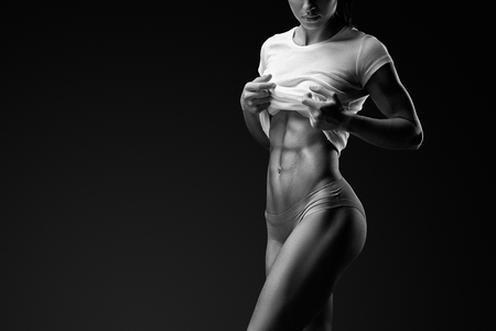 Photo for Black and white portrait of young woman with muscular body standing against black background. Image of fitness woman in sports clothing. - Royalty Free Image